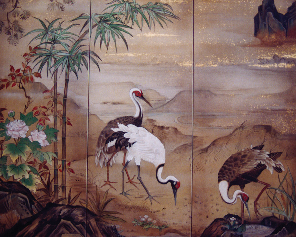 Asian inspired mural of cranes with mountains in the background