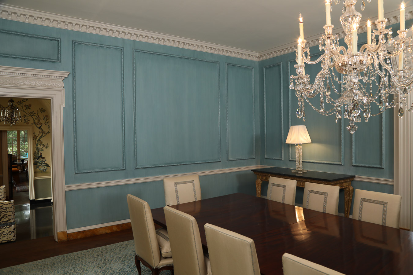 Pale blue glazed wood panels in dining room with crystal chandelier