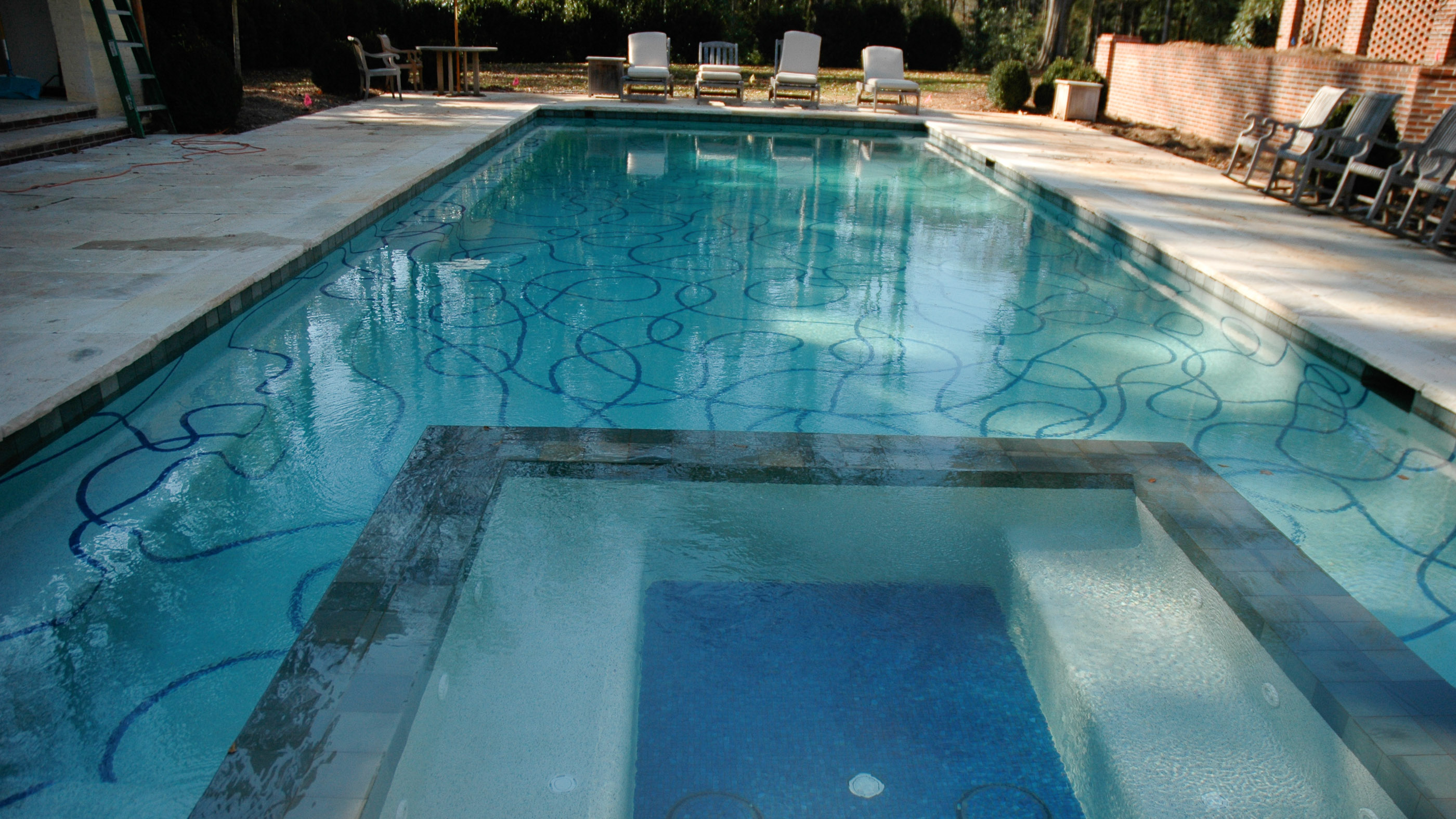 View of swimming pool lined with tile ribbons decorating the pool basin