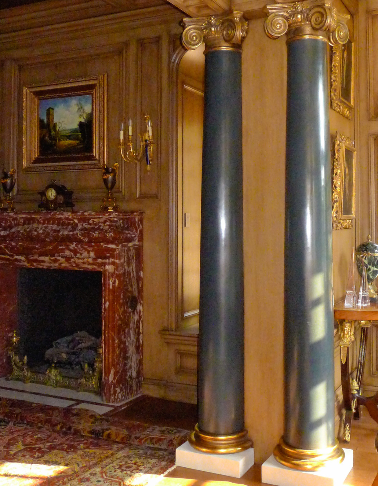 Interior view of two blue finished columns and gilded details for an opulent room with fireplace in the background