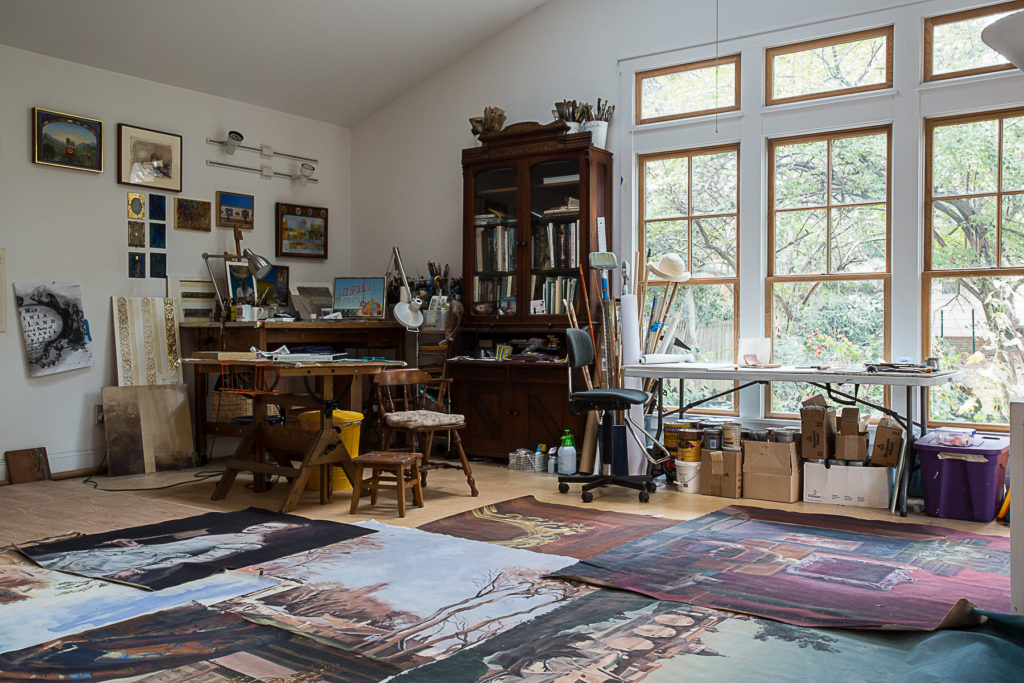 Jill Biskin studio space with tall windows, drafting table and numerous canvases spread out on the floor